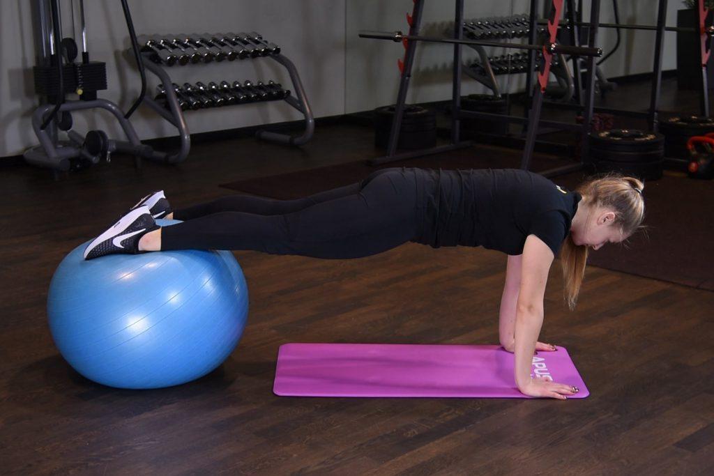 Deska z wyprostowanymi ramionami oraz stopami na piłce do ćwiczeń