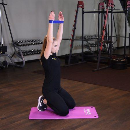Rozszerzanie ramion w klęku z gumą mini band nad głową