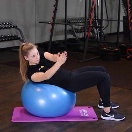 Rotacja tułowia w spięciu brzucha na piłce do ćwiczeń