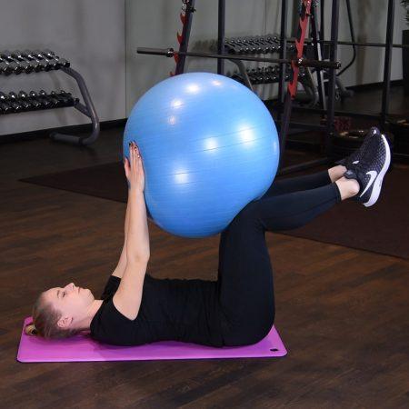 Wciskanie piłki do ćwiczeń w kolana w leżeniu na plecach