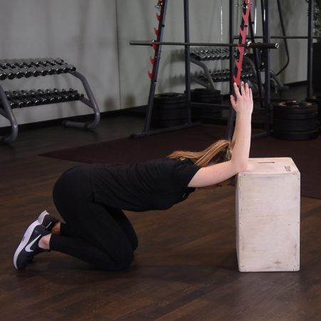 Rozciąganie mięśni najszerszych grzbietu i tricepsów w klęku z łokciami na podwyższeniu